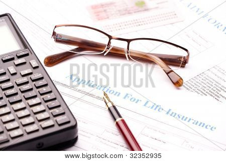 Blank application for life insurance with fountain pen, calculator and glasses. Other documents like ID etc in the bacground