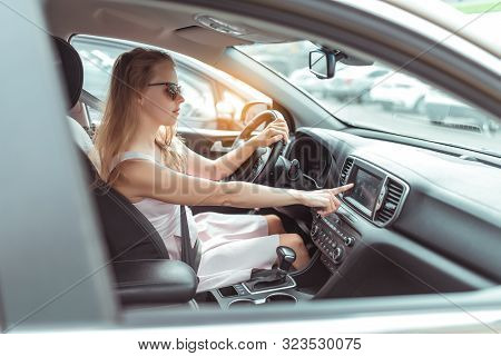A Woman In Car, Selects Navigation Application On Touch Screen Display. Pink Dress. Automatic Gearbo