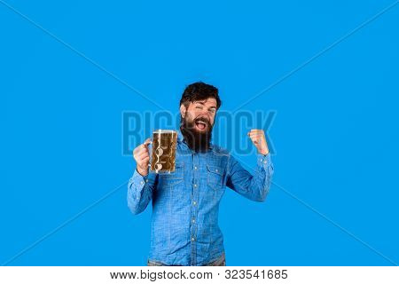 Man drinking draught beer at bar or pub. Bearded man holds glass with delicious ale. Man tasting draft beer. Oktober fest. Bearded hipster drinking beer. Happy man with mug of craft beer. Oktoberfest poster