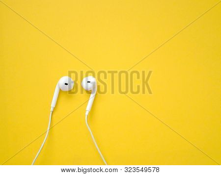 White Earphones On Yellow Background. Earphones For Listening To Music And Sound On Portable Devices