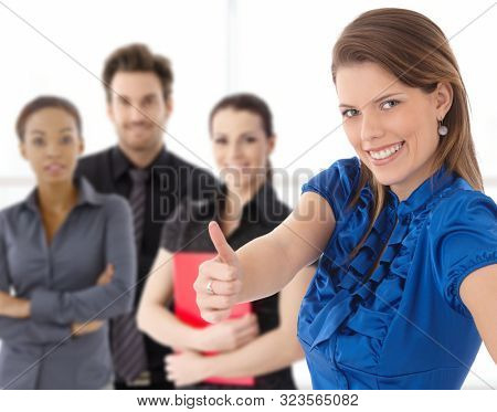 Portrait of happy young businesswoman looking at camera showing thumb up, smiling, business team in background.