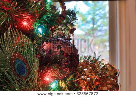 Festive holiday ornaments on a Christmas tree make a colorful background.  There is copy space if needed.