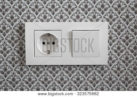 White Plastic Switched Double Socket. Light Switch And Power Socket Control Panel On Wall With Wallp