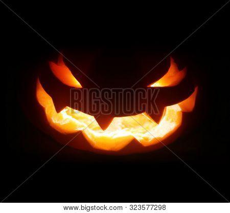 Spooky Halloween jack o lantern face glowing in the dark