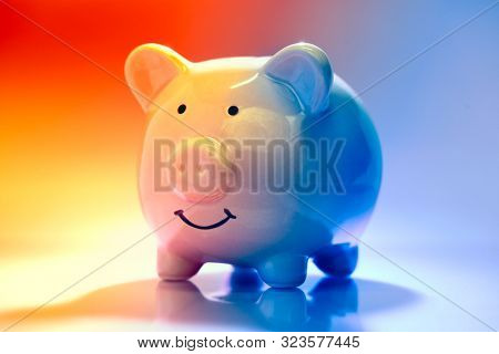Smiling Piggybank on red and blue background. Saving vs spending money concept.