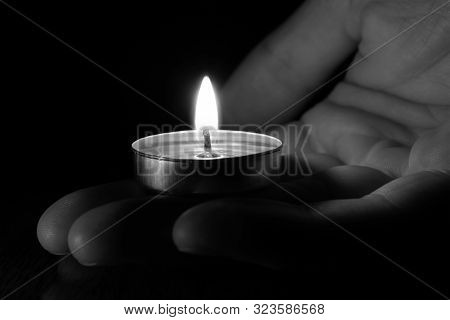 Close-up Candle In Hand Burning In The Black Background. Black And White Photo. The Concept Of Mourn