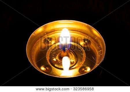 Close-up Candle Burning In The Black Background. The Concept Of Mourn, Grief Or Mourning.