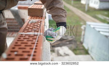Worker Wipes The Seams Outside The Brick House. The Builder Processes The Brickwork. Construction Ma