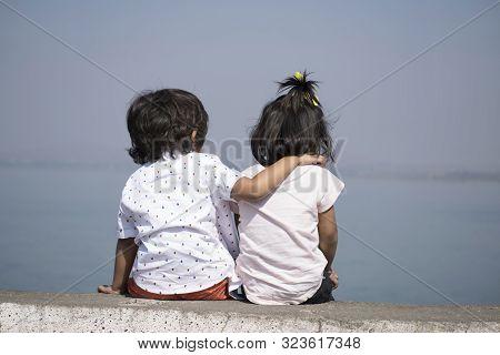Boy And Little Girl Sitting Near Lake At Veer Dam In Pune, Maharashtra, India.