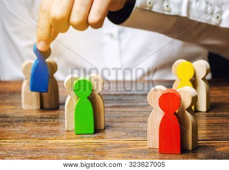 Groups Of Multicolored Wooden People And Businessman. The Concept Of Market Segmentation. Target Aud