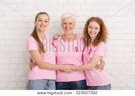 Breast Cancer Concept. Three Happy Women Of Diverse Age Wearing Pink Ribbon T-shirts Hugging Over Wh