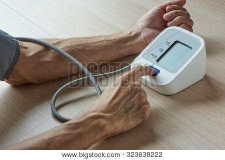 A Male Person Taking Self Measurement Of Blood Pressure At Home With Pressure Cuff Around The Arm