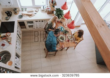 Loving Parents Having Dinner With Their Cute Daughter At Home