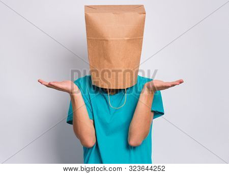 Portrait of teen boy with paper bag over head showing helpless gesture with hands - I do not know. Teenager cover head with bag, isolated on white background. Child making helpless sign.