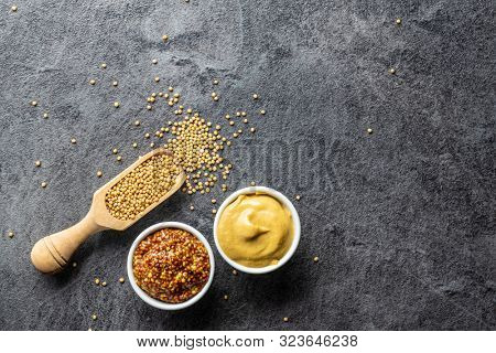 Yellow mustard and whole grain mustard and mustard seeds on kitchen table. Top view.
