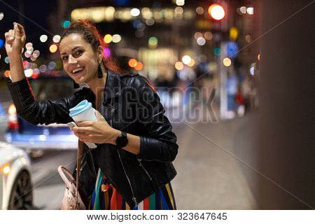 Woman calling taxi on city street at night