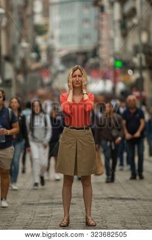 Depressed young woman covers his eyes with his hands at standing in the middle of a crowded street. Panic attack in public place.