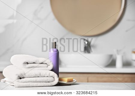 Folded Towels And Toiletries On Marble Table In Bathroom, Space For Text