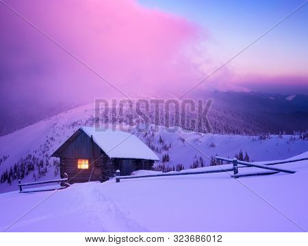 Christmas landscape with a wooden house in the mountains. Beautiful winter sunrise