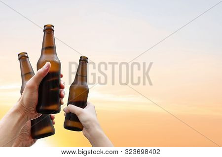Hands Holding Three Beer Bottles And Happy Enjoying Harvest Time Together To Clinking Glasses At Out