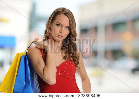 Young girl with shopping bags outside a mall