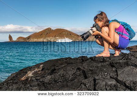 Galapagos tourist photographing marine iguana on Santiago Island in Galapagos Islands. Cruise ship and Pinnacle Rock and Bartolome Island in background. Famous Galapagos cruise ship tour destination.