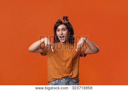 Pretty Brunette Woman In A T-shirt And Beautiful Headband Pointing With Her Fingers At The Down Side