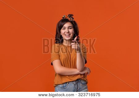 Pretty Brunette Woman In An Orange T-shirt And Headband Holding Thumbs Up Expressing Positive Evalua
