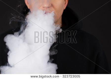 Vaping White Man Holding A Mod. A Cloud Of Vapor. Black Background. Vaping An Electronic Cigarette W