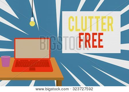 Text sign showing Clutter Free. Conceptual photo Well organized and arranged Tidy All things in right places Front view open laptop lying on wooden desktop light bulb falling glass. poster