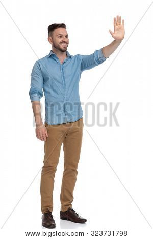 side view of a beautiful casual man with blue shirt  standing and waving his hand happy on white studio background