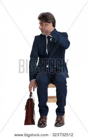 intrigued formal business man with navy suit and briefcase is sitting and doing a are you crazy gesture to a side on white studio background