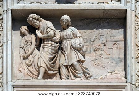MILAN, ITALY - JUNE 22, 2018: Lot and his daughters flee from Sodom, marble relief on the facade of the Milan Cathedral , Duomo di Santa Maria Nascente, Milan, Lombardy, Italy