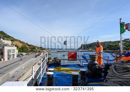 Santa Teresa, Sardinia - September, 2019. A Man In Overalls Winds A Rope On A Ferry In The Port