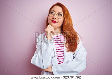 Young redhead doctor woman wearing glasses over pink isolated background with hand on chin thinking about question, pensive expression. Smiling with thoughtful face. Doubt concept.