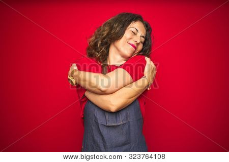 Middle age senior woman wearing apron uniform over red isolated background Hugging oneself happy and positive, smiling confident. Self love and self care
