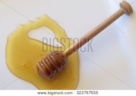 A Wooden Dipper Used For Serving Honey.