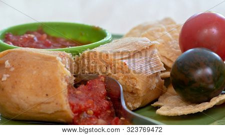 Closeup On Fork Cutting Unwrapped Tamale Served With Sweet Corn Tortillas And Tomato Sauce On Green
