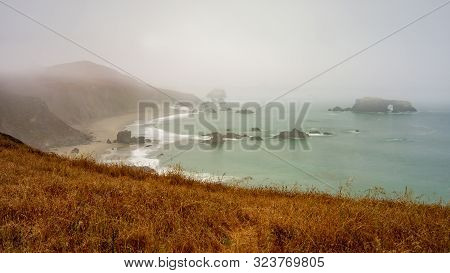 Landscape View Of Foggy Sonoma Coast In California, Usa, By The Arch Rock Beach State Park On A Typi
