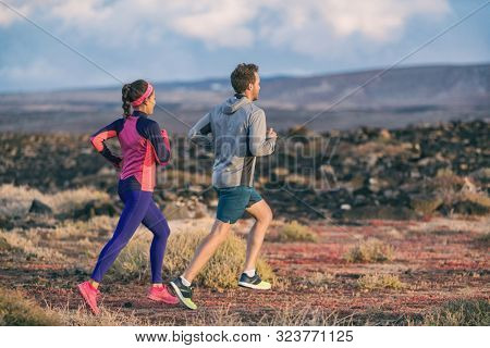 Running people training together active couple healthy lifestyle jogging in autumn outdoor. Happy man and woman friends exercising outside.