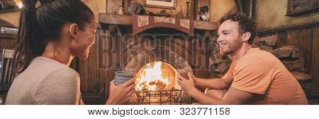Cozy fireplace home lifestyle couple drinking hot cocoa cup at winter cottage getaway romantic weekend banner panoramic.