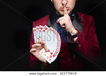 Disclosure Of Focus. Magician Shows Trick With Playing Same Cards On Dark Background