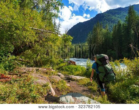 A Female Tourist With A Backpack Climbs Along The Path Along The River. Warm Sunny Day.