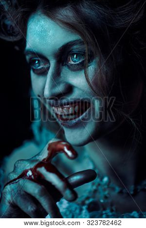 Halloween. Close-up portrait of a bloodthirsty woman vampire in the old abandoned castle. Vintage style.