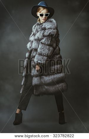 A full length portrait of a young fashionable woman in a fur coat. Beauty, fashion.