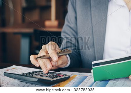 Businesswoman On Desk In Office Using Calculator To Calculate Saving Account Passbook And Statement