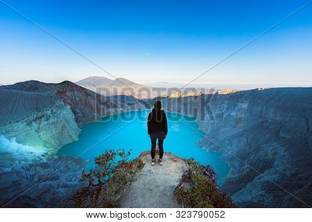 At Sunrise Girl Stand On Rock Under Volcano Kawah Ijen Crater. Look At Largest In World Acid Lake, S