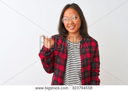 Young chinese woman wearing t-shirt jacket and glasses over isolated white background smiling with happy face looking and pointing to the side with thumb up.
