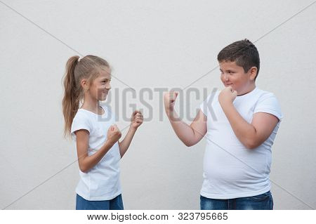 Gender Issues Concept Of Two Kids Little Thick Boy Against Small Thin Girl Holding Fist Ready To Fig