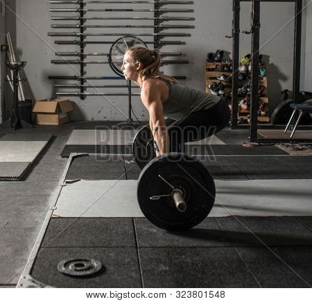 Strong female weight lifter getting ready to lift heavy barbell in grungy gym.